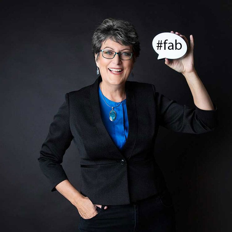 Ingrid Moyle in a dark suit and blue shirt holding a hashtag #fab.